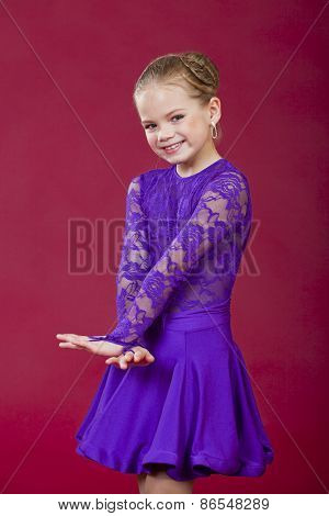 Portrait of a charming little girl looking at camera, isolated on red background