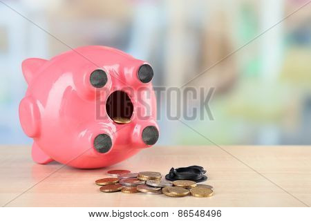 Opened piggy bank with coins on wooden table, on white background