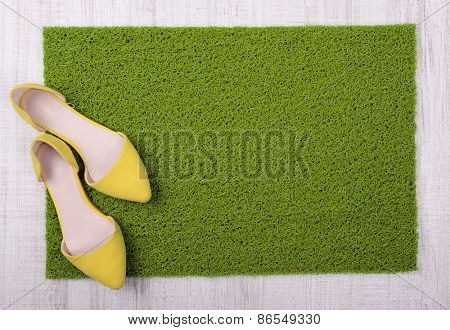 Green carpet on floor and female shoes on it