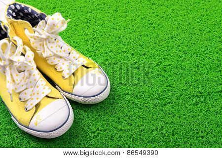 Sneakers on green carpet background