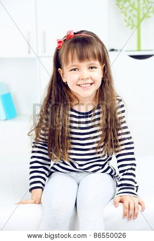 Portrait of cute little girl on home interior background