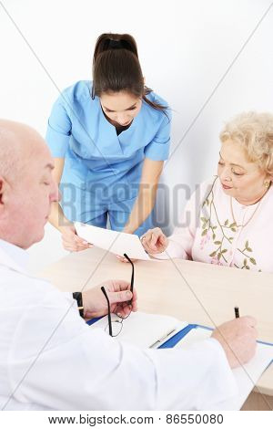 Happy doctors and patient in hospital clinic
