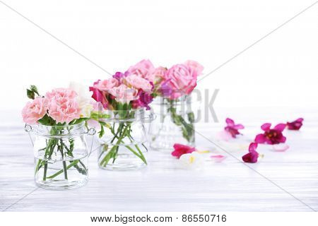 Beautiful spring flowers in glass bottles isolated on white
