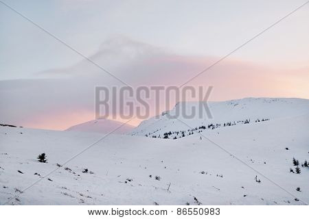 Sunset sky with clouds over snowdrifts
