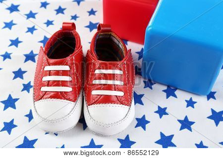 Baby shoes on spotted white background