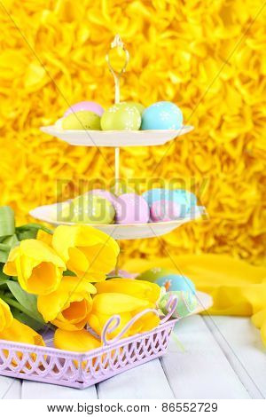 Easter eggs on vase and tulips on table on yellow background