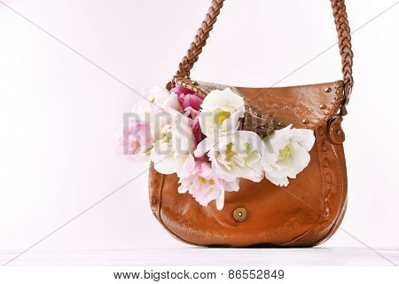 Beautiful tulips with brown bag isolated on white