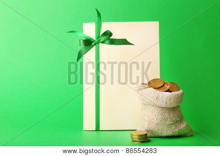 Greeting card for Saint Patrick's Day with bag of coins on green background