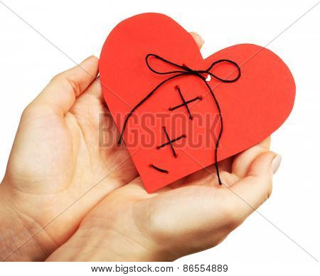 Female hands holding stitched heart isolated on white