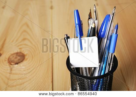 Pens in metal holder on wooden table background