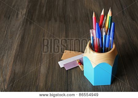 Colorful pens and pencils in cup on wooden table background