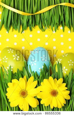 Easter eggs and grass on colorful paper background
