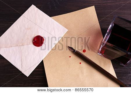 Envelope with pen and ink on wooden background