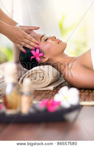 young woman receiving head massage in spa environment