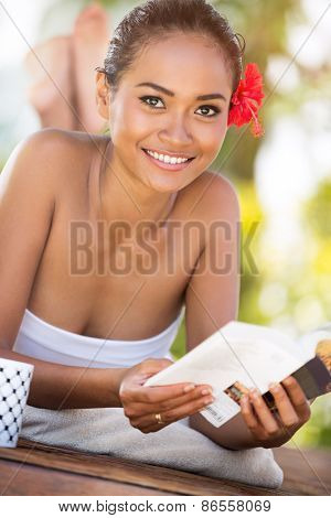 Cheerful woman with book, Balinese woman relaxing