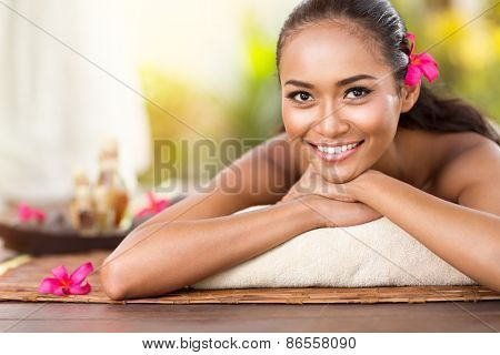 Beautiful smiling girl outdoor portrait at massage spa. Serene happy Balinese woman relaxing looking joyful at camera