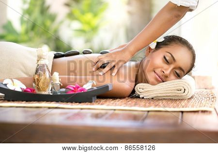 Stone massage, beautiful woman getting spa hot stones massage in spa salon