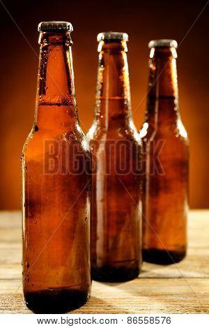 Glass bottles of beer on wooden table on dark background