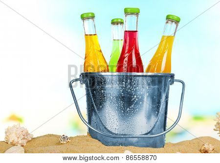 Bottles of tasty drink in metal bucket with ice on sand on bright background