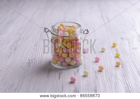 Colorful sprinkles on jar on table close-up