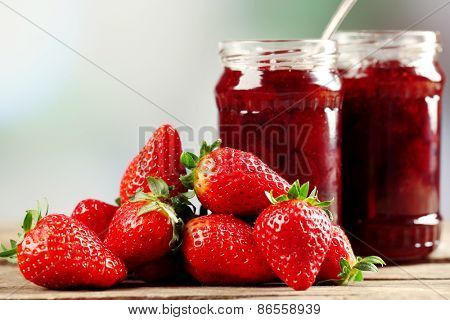Jars of strawberry jam with berries on table on bright background