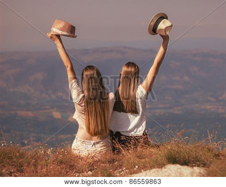 Girls happy on mountain with hats