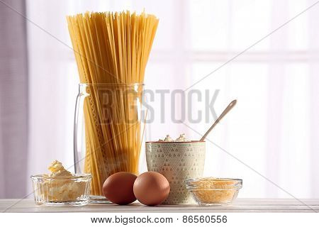 Different products on wooden table on blurred window background