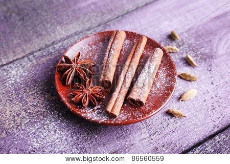 Spices in plate with powdered sugar on color wooden table background