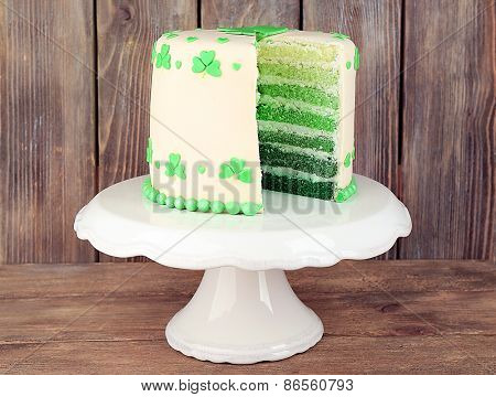 Sliced cake for Saint Patrick's Day on stand and wooden background
