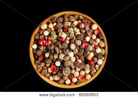 Pepper in wooden bowl, isolated on black