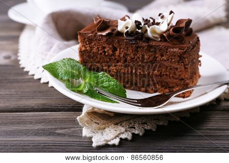 Tasty piece of chocolate cake with mint on wooden table background