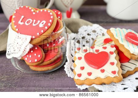 Heart shaped cookies for valentines day, teapot and cups on color wooden background