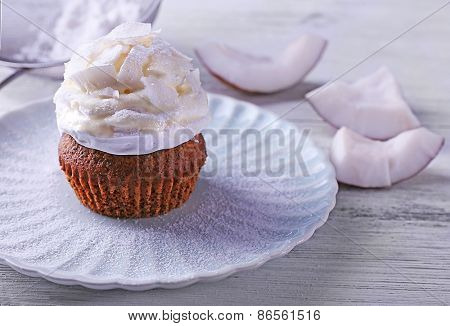 Delicious coconut cupcake with cream on wooden table background