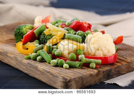 Frozen vegetables on cutting board, on napkin, on wooden table background