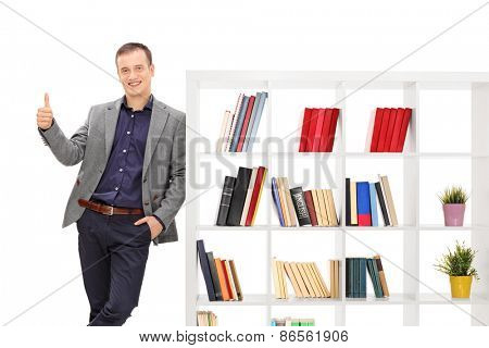 Young guy in a gray coat leaning on a bookshelf and giving a thumb up isolated on white background