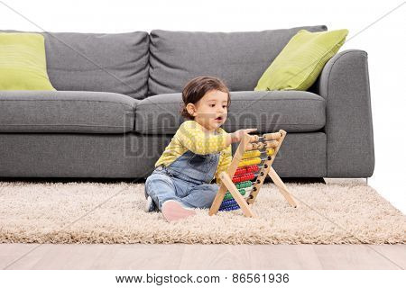 Little girl playing with an abacus seated on the floor by a modern gray sofa isolated on white background