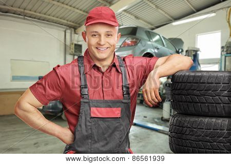 Cheerful male mechanic leaning on a stack of tires and posing in a garage with a car behind him
