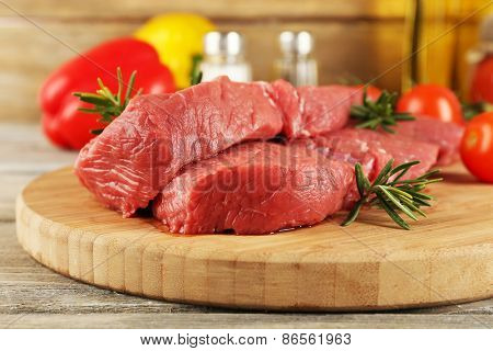Raw beef steak on cutting board with vegetables and spices on wooden background