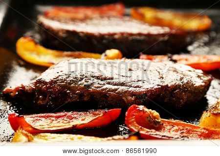 Composition with tasty roasted meat and sliced pepper on pan, tomatoes and rosemary sprigs on wooden background