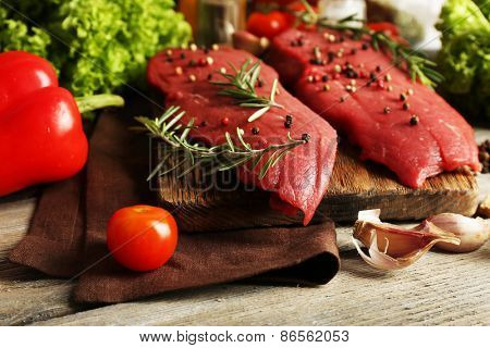 Raw beef steak with spices and greens on table close up
