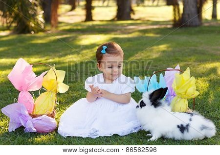 Smiling Baby Girl Looking At Rabbit With Easter Chocolate Eggs