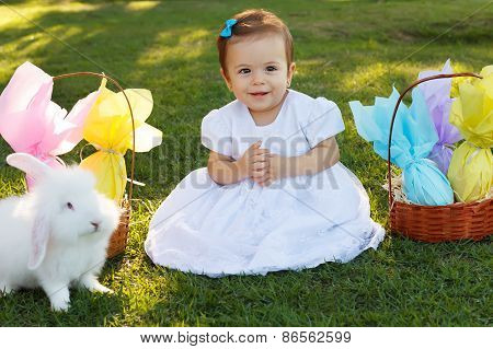 Smiling Baby Girl With Basket With Chocolate Eggs, White Rabbit For Easter