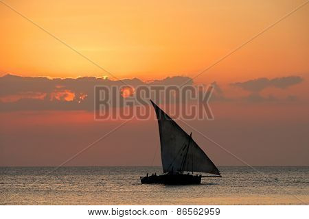 Sailboat (dhow) on water at sunset with clouds, Zanzibar island