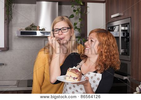 Delighted Girlfriends Eating Cake In The Kitchen