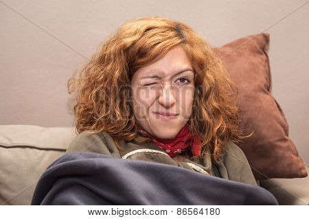 Redhead Woman With One Eye Closed Relaxing On Sofa