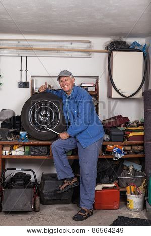 Happy Senior Worker With A Tire In Garage