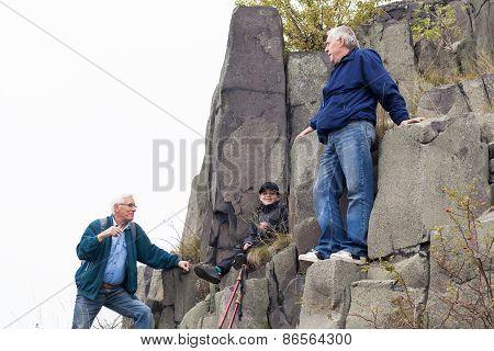 Seniors And Child Trekking On The Rock