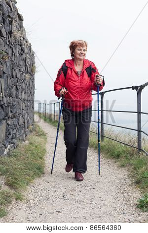 Senior Woman Nordic Walking On Rocky Trail