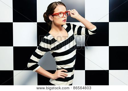 Fashion shot of an elegant model in glasses posing in dress in black and white stripes on a background of black and white squares. Beauty, fashion concept. Business style.