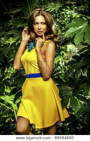 Attractive young woman  among the tropical plants. Vacation. Tropics. Fashion shot.